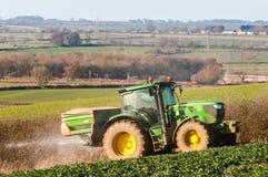 Spalmatore del fertilizzante e del trattore nel campo Fotografia Stock