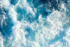 Spalsh of a blue sea water behind a ship. royalty free stock images
