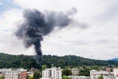 Spalte des schwarzen Rauches steigend über Wohngebäude Stockfoto