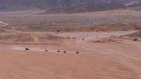 Spalte eines Viererkabelfahrrades fährt durch die Wüste in Ägypten auf Hintergrund von Bergen Fahren von ATVs stock video footage