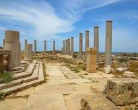 Spalten gegen blauen Himmel mit weißen wispy Wolken an den alten römischen Ruinen von Leptis Magna in Libyen lizenzfreie stockbilder