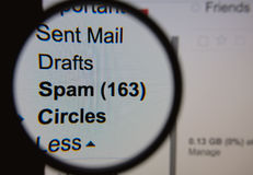 Spam. Magnifying glass showing a spam folder in the mailbox on the monitor screen stock photos