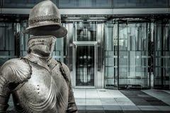 Spam.Medieval-harnesk som skyddar en affärsbyggnad. Begrepp av f Arkivbilder
