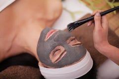 SpaMud maskerar Kvinna i brunnsortsalong Framsidamaskering Ansikts- Clay Mask behandling arkivbilder