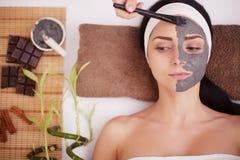 SpaMud maskerar Kvinna i brunnsortsalong Framsidamaskering Ansikts- Clay Mask behandling Arkivfoton