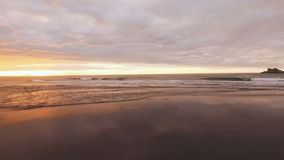 Span along the ocean waves. Reflection of sun and clouds in the water. Beautiful background. stock footage