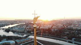 The span of the angel on the steeple in the Peter and Paul Fortress at sunset - aerial shooting of the historical center. Epic air flight near the angel on the stock footage
