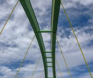 Span of an arched bridge against a blue sky with clouds royalty free stock images
