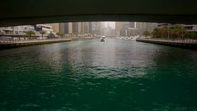 The span of the camera under the bridge following behind the floating boat in Dubai Marina stock video