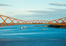 A span of the Forth Rail Bridge with some oil industry support v. Essels and a train crossing the bridge, viewed from the footpath of the Forth Road Bridge royalty free stock images