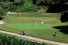 Women on a putting green, Marbella, Spain. Two women playing golf on the putting green at the Rio Real Golf Club, Marbella, Costa del Sol, Malaga Province royalty free stock image