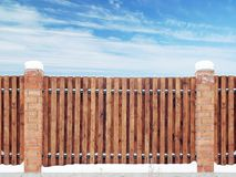 Span of the new wooden fence between the brick pillars. Winter view against the blue sky royalty free stock photos