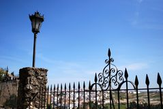 Ornate ironwork fence with views over part of the town and countryside, Ronda, Spain. Ornate ironwork fence with views over part of the town and countryside stock image