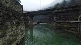 Span over the river near destroyed suspension bridge stock footage