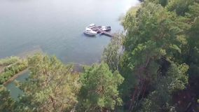 Span through pine trees on a drone to expensive yachts stock footage