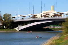 Christ of Expiration bridge, Seville, Spain. Rowers along the Guadalquivir river with the Christ of Expiration bridge to the rear, Seville, Seville Province royalty free stock photo