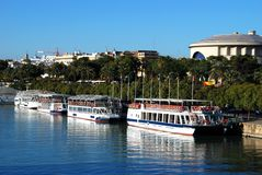 Tour boats moored along the river, Seville, Spain. Tour boats moored along the Guadalquivir river with the Maestranza theatre to the rear, Seville, Seville royalty free stock photo