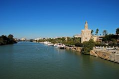 View along the river Guadalquivir, Seville, Spain. View along the Guadalquivir river with the golden tower Torre del Oro on the right hand riverbank, Seville royalty free stock photography
