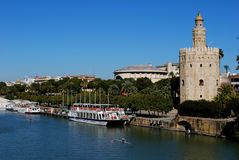 Torre del Oro along the riverbank, Seville, Spain. View along the Guadalquivir river with the golden tower Torre del Oro on the riverbank, Seville, Seville stock photography