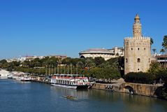 Torre del Oro and river Guadalquivir, Seville, Spain. View along the Guadalquivir river with the golden tower Torre del Oro on the riverbank, Seville, Seville stock image