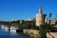 Torre del Oro along the riverbank, Seville, Spain. View along the Guadalquivir river with the golden tower Torre del Oro and tour boats along the riverbank stock photo