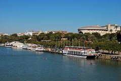 River Guadalquivir and Maestranza theatre, Seville, Spain. View along the Guadalquivir river with the Maestranza theatre to the rear, Seville, Seville Province stock image