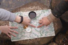 Spana turister planerar rutten, orienterar på terrängen på översikten och kompasset ovanför sikt arkivbilder