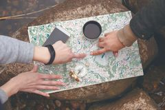 Spana turister planerar rutten, orienterar på terrängen på översikten och kompasset ovanför sikt arkivbild