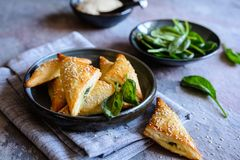 Spanakopita triangles stuffed with spinach and Feta cheese. Freshly baked Spanakopita triangles stuffed with spinach and Feta cheese stock images