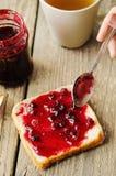 Spanda l'inceppamento del mirtillo rosso su pane immagini stock libere da diritti
