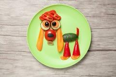Spaniel som göras av grönsaker på plattan och tabellen Arkivfoton