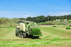 Spanien Catalonia, mars 19, 2017 Traktor i fältet som mejar al Arkivbilder