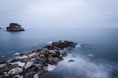 Spanien, Màlaga, Peñol-del Cuervo: Felsen auf dem Strand und den seidigen Wellen stockfotografie