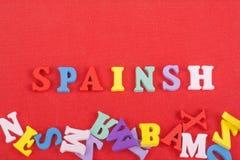 SPANIEN-Wort auf dem roten Hintergrund verfasst von den hölzernen Buchstaben des bunten ABC-Alphabetblockes, Kopienraum für Anzei Stockbilder