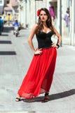 Spanierin im schwarzen Kleid wirft in der Stadt auf Stockbild