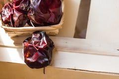 Spanisch trocknete nyora Pfeffer auf Thread im Weidenkorb, auf hölzernem Kasten, helle rote Farbe, Sonnenlicht Stockfotos