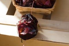 Spanisch trocknete nyora Pfeffer auf Thread im Weidenkorb, auf hölzernem Kasten, helle rote Farbe, Sonnenlichtfleck Stockfoto