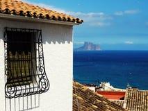 Spanisch zerrieb Fenster des alten Hauses und des Meeres im Hintergrund lizenzfreies stockfoto