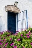 Spanische blaue alte Einstiegstür mit dem offenen Tor im weißen Haus Stockfotos