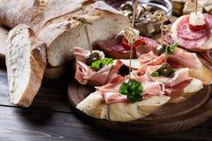 Spanische Tapas mit Scheiben jamon serrano, Salami, Oliven und Käsewürfeln auf einem Holztisch Stockbild