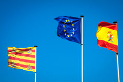 Spanische und europäische Flaggen, die in den Wind wellenartig bewegen Lizenzfreie Stockfotografie