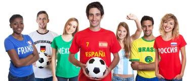 Spanischer Fußballfan mit Ball und zujubelnde Gruppe anderer Fans Stockbild