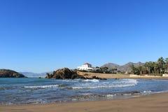 Spanischer Meerblick eines sandigen Strandes mit zusammenstoßenden Wellen lizenzfreies stockbild