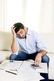 Spanischer mexikanischer Geschäftsmann sorgte sich Lohnlisten auf Couch Lizenzfreies Stockfoto