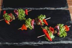 Spanischer Snack, banderillas auf Aufsteckspindeln Pfeffer mit der Salami-, In Essig einlegenoliven, der Essiggurken, Grünen und  lizenzfreies stockbild