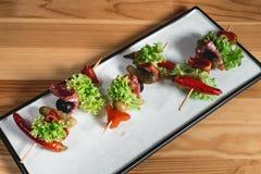 Spanischer Snack, banderillas auf Aufsteckspindeln Pfeffer mit der Salami-, In Essig einlegenoliven, der Essiggurken, Grünen und  stockbilder