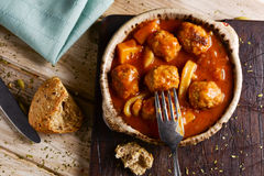 Spanish albondigas con sepia, meatballs with cuttlefish. High-angle shot of an earthenware bowl with typical spanish albondigas con sepia, meatballs with Royalty Free Stock Photos