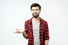 Spanish angry and discontented man spreading his hand and ask what do you mean. Against a gray background stock photography