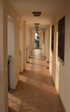 Spanish Apartment Hallway. The outdoor hallway of a Spanish apartment block, with the sun's rays slanting across the floor Royalty Free Stock Images