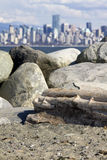 Spanish Banks, with Vancouver skyline behind. Rock and log pile on the beach at Spanish Banks, with Vancouver skyline behind royalty free stock photo